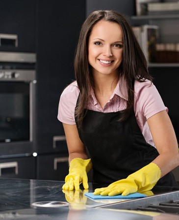 A cleaning professional cleaning a kitchen in London